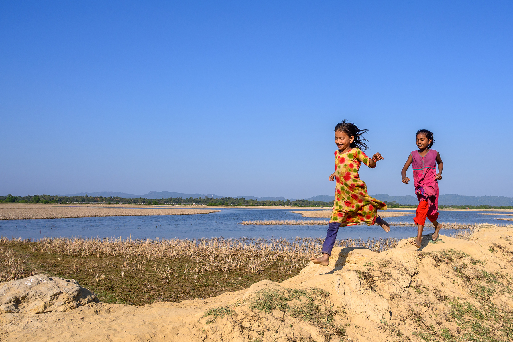 Children run along a lake in Bangladesh