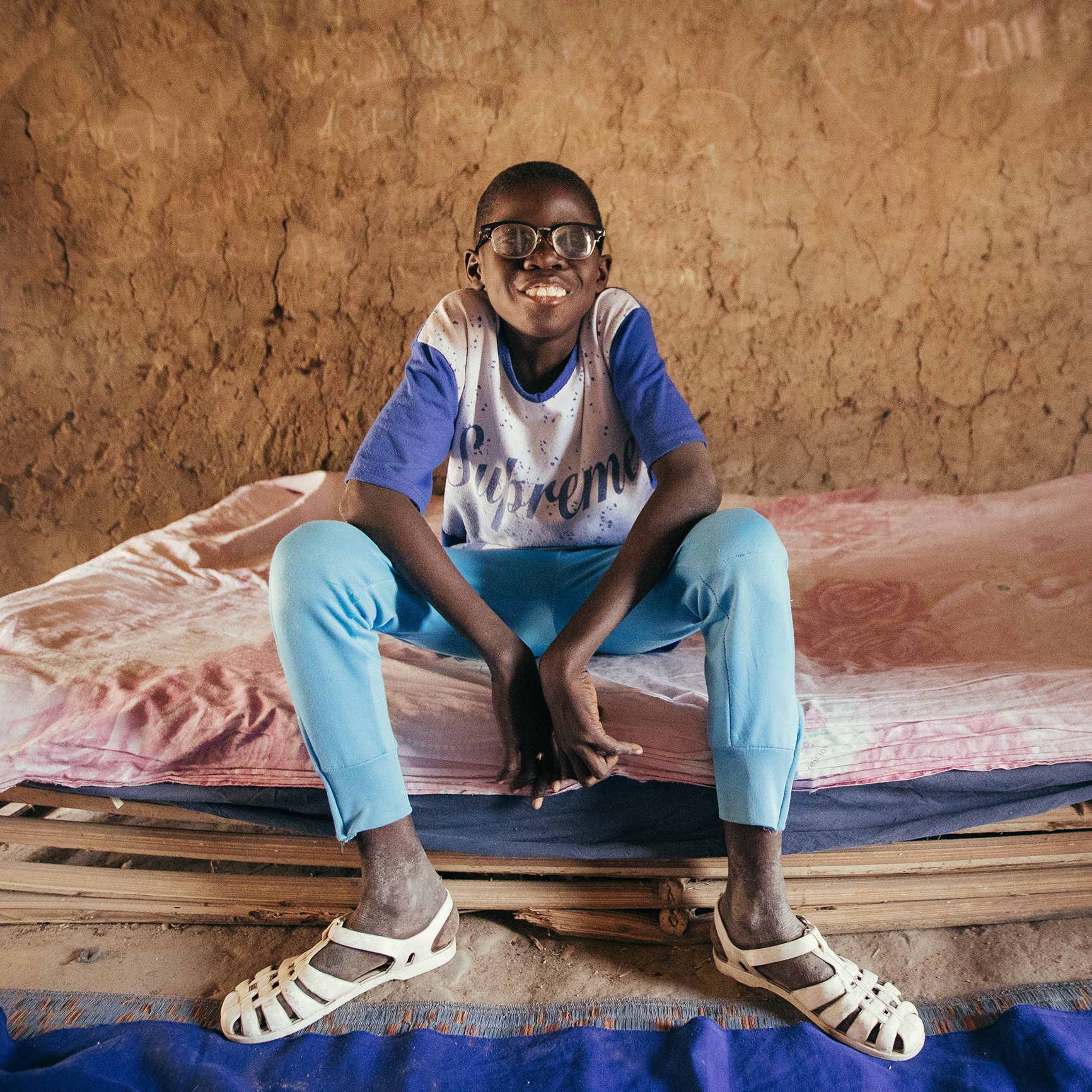 Boubacar sits on his bed in his room