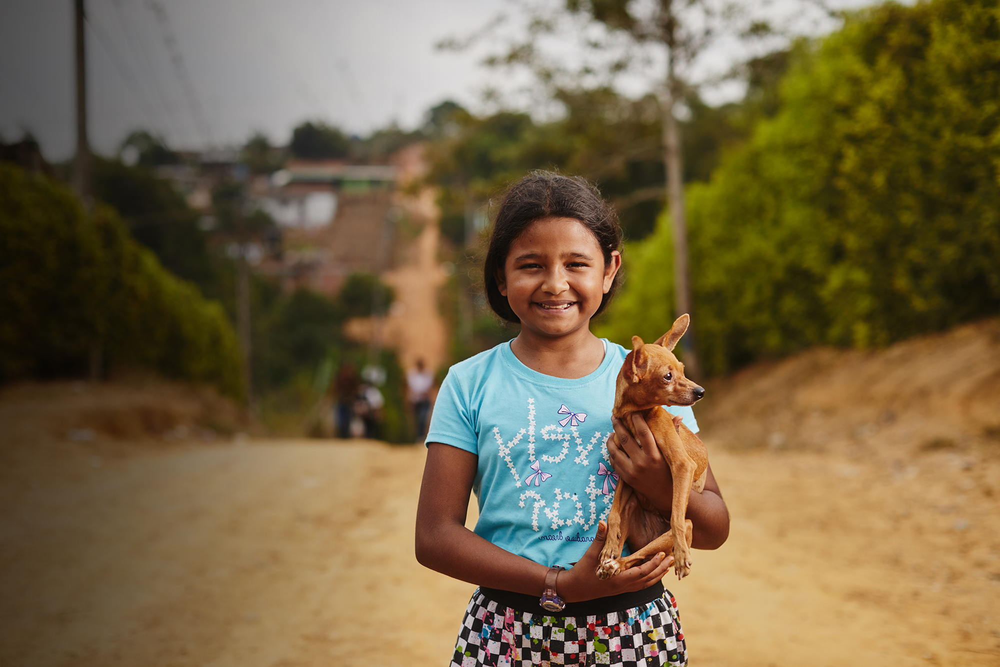 A girl in Colombia holds a puppy