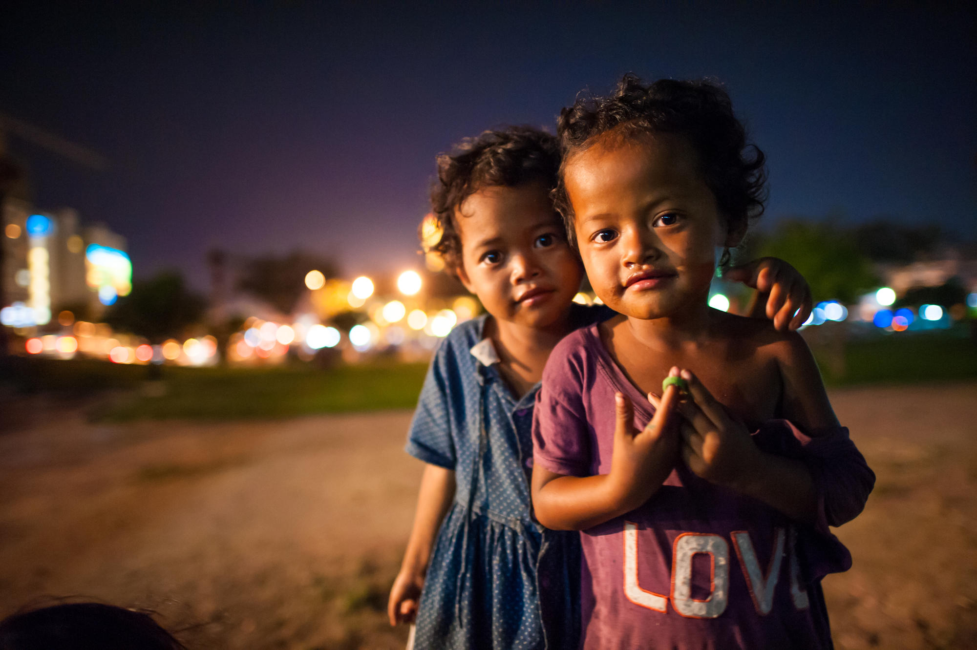 Two young Khmer children stand in the street