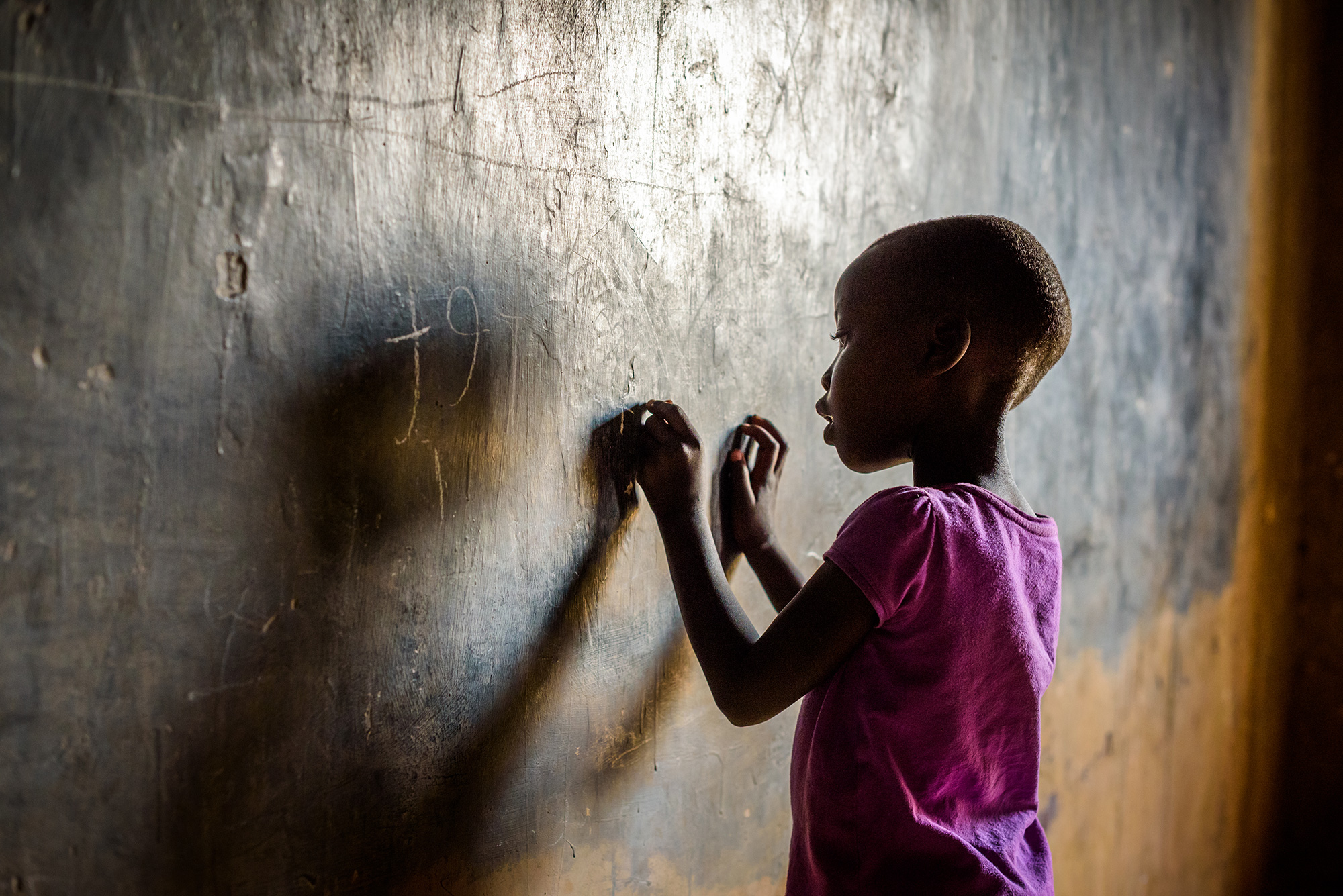 An African girl writes on a Chalkboard