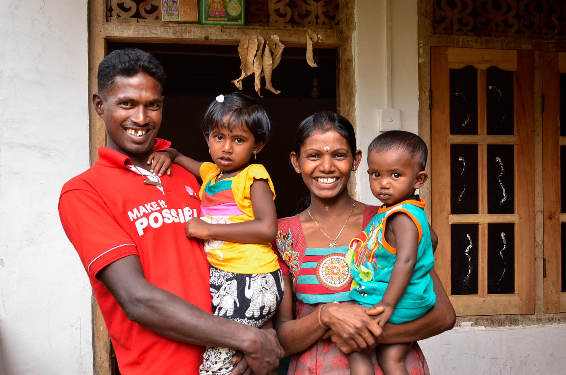 A sri lankan family smiles in front of their home