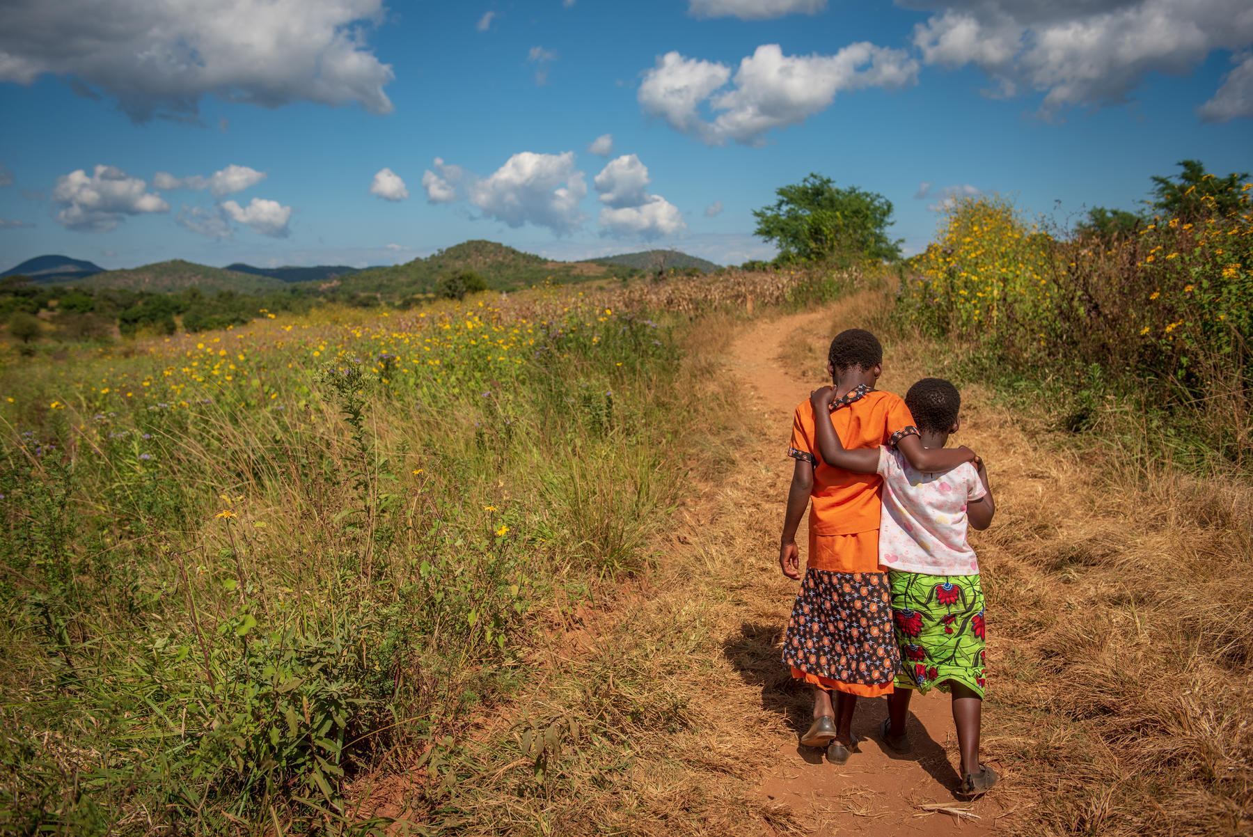 Two children walk down a road in Africa