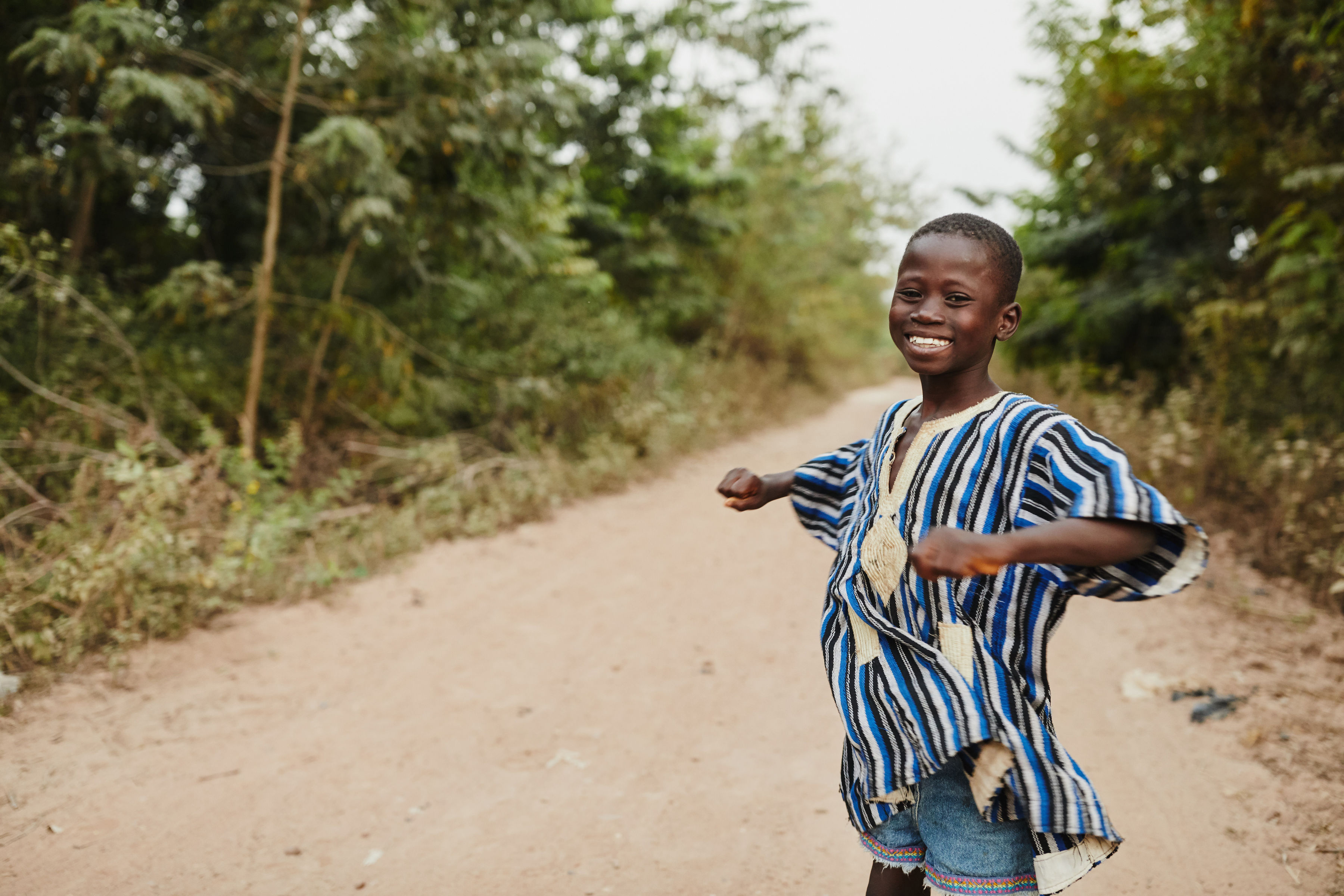 A boy dances on a road in Ghana