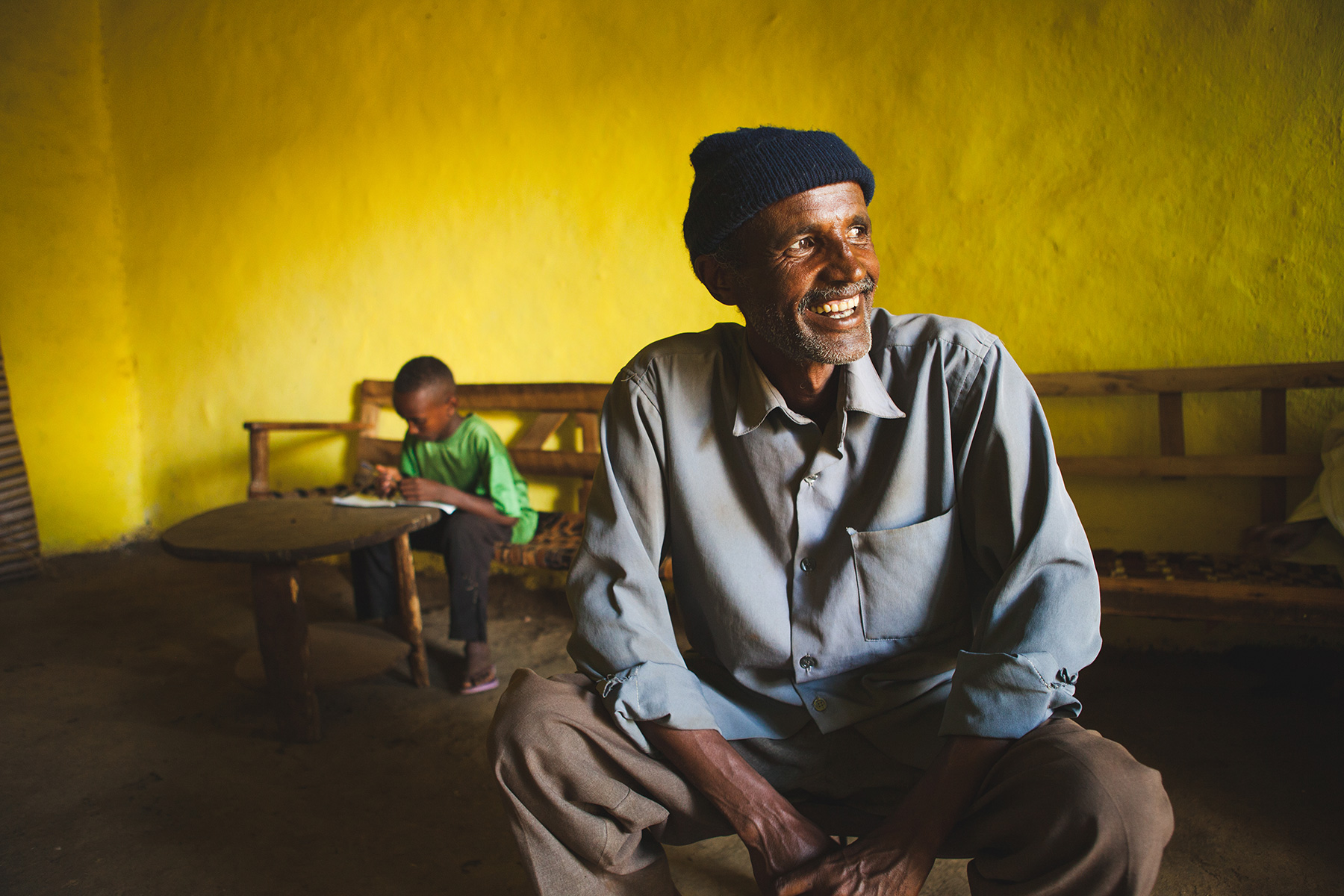 An Ethiopian man in his home with his son reading in the background
