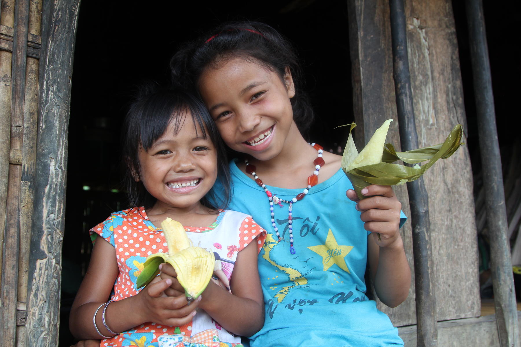 Two Vietnamese children hold flowers at their home