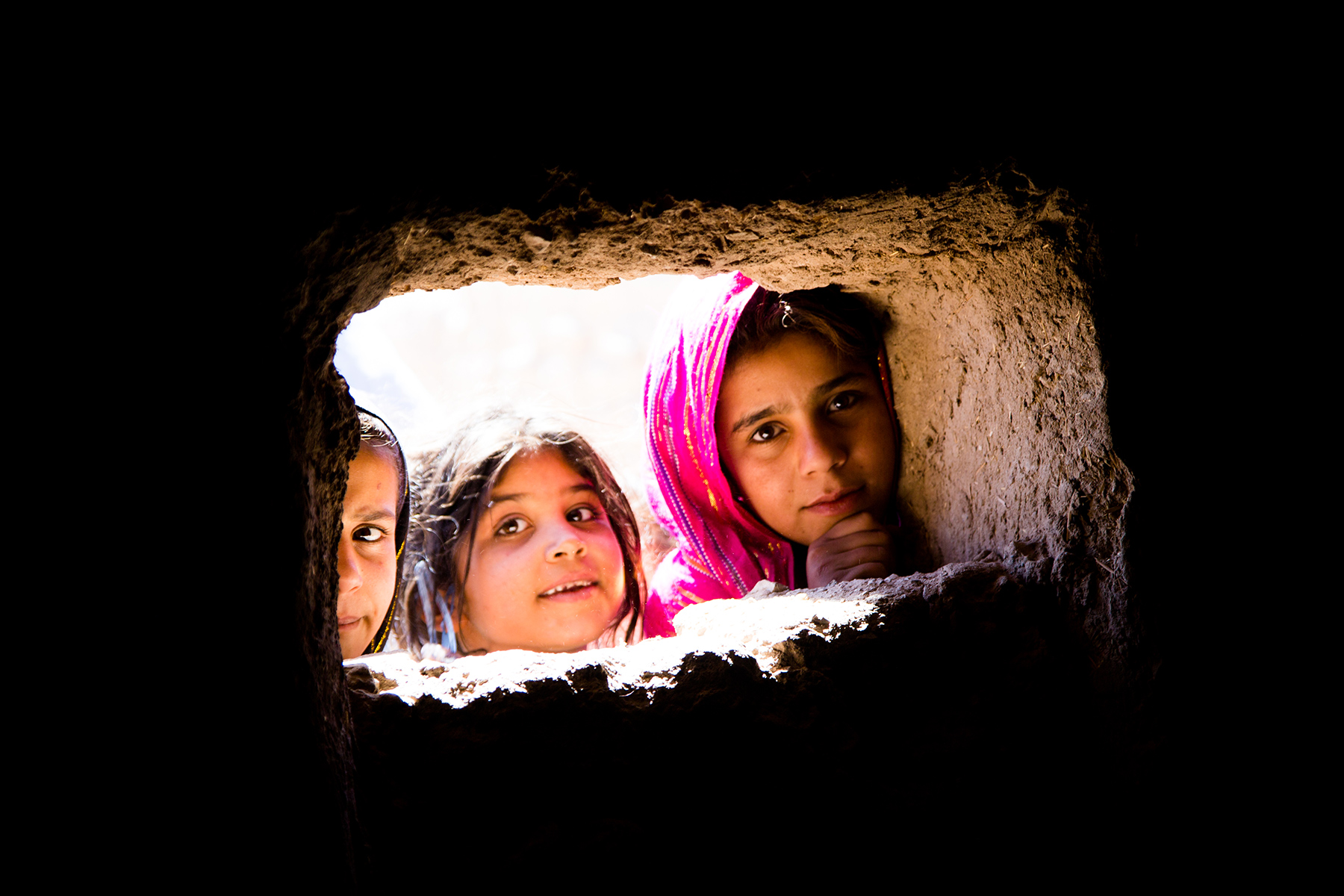 Children in Afghanistan look in a well