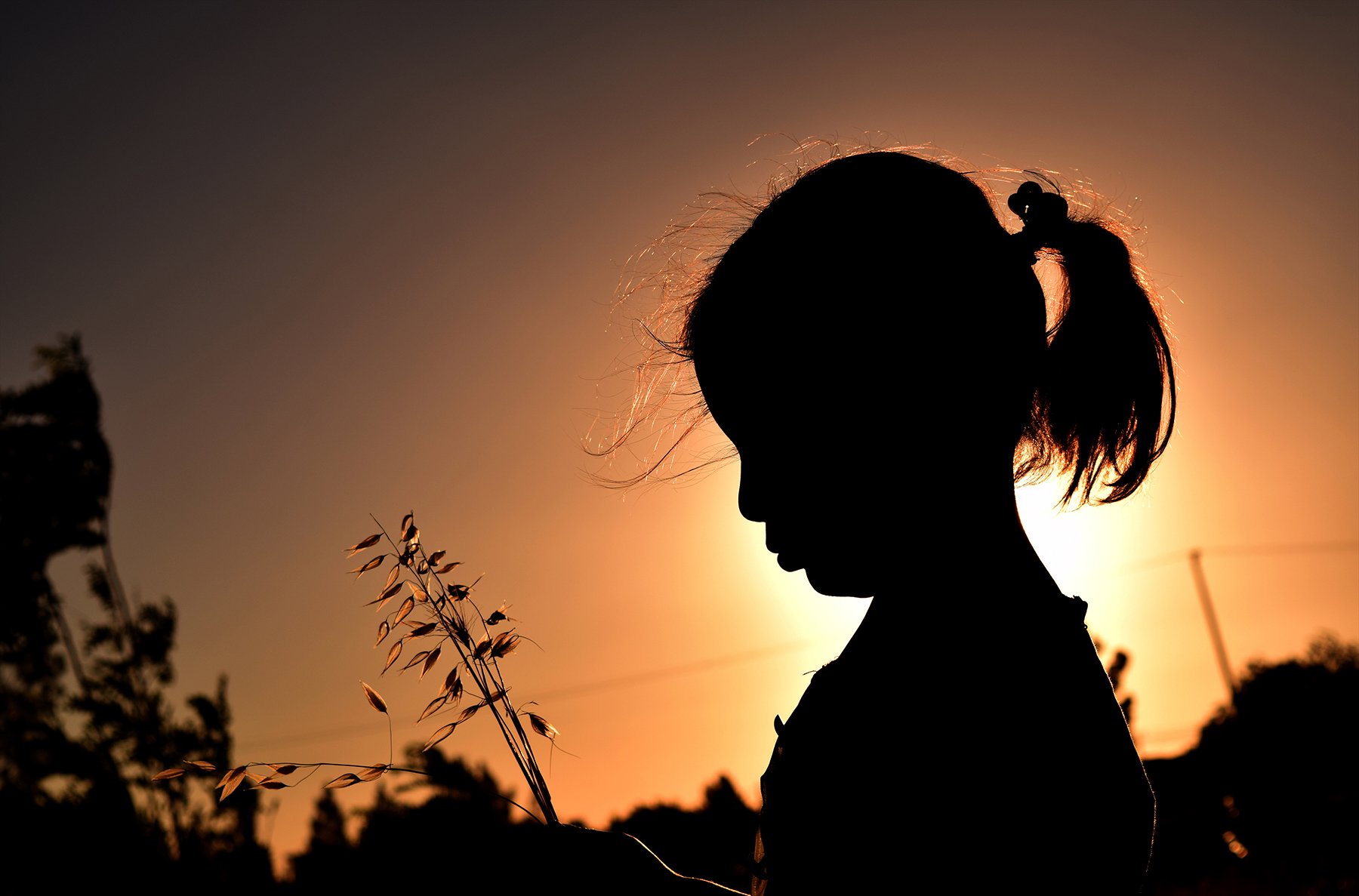 An afghan girl stands with the sun setting behind her