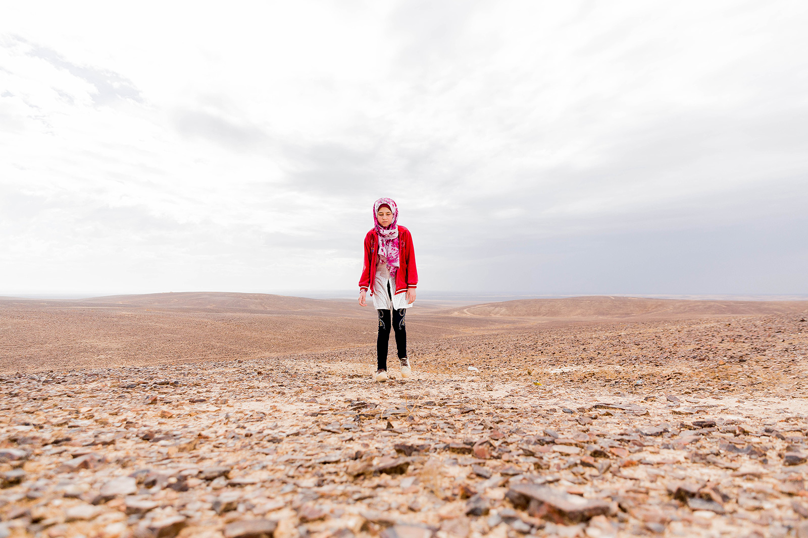 Shaima walks outside the refugee camp in syria