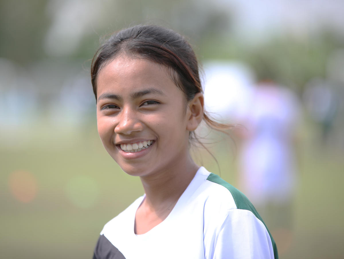Khmer teenager in football jersey smiles on football pitch
