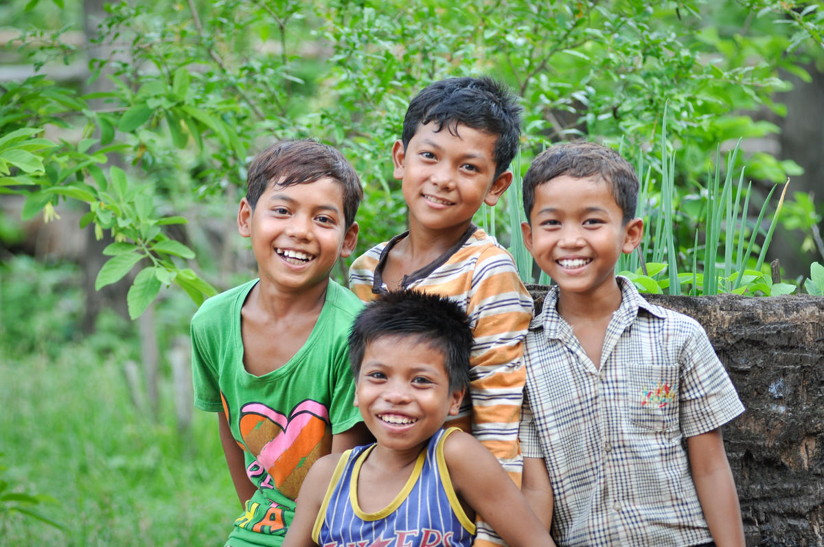 Four Khmer boys smiling at camera standing in garden