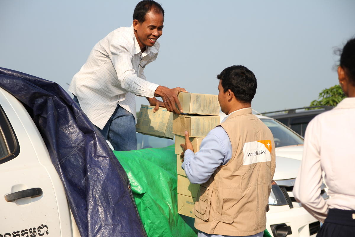 Two men from the World Vision emergency response team unload food supply boxes from the back of a white ute