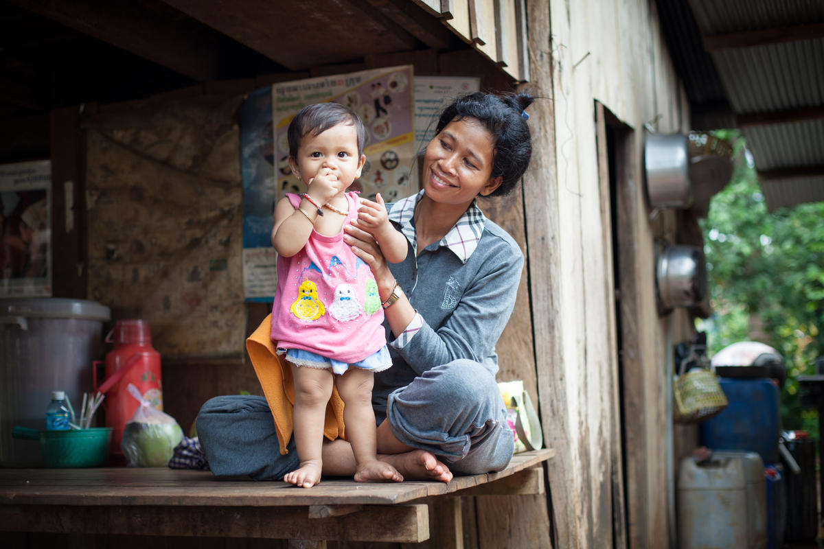 Khmer mother smiles as she holds up her baby toddler so she is standing