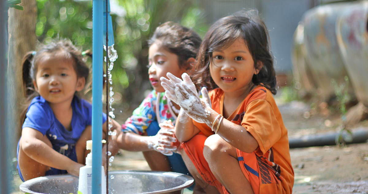 Three Khmer girls wash their hands in a bucket from a tap installed by World Vision Cambodia
