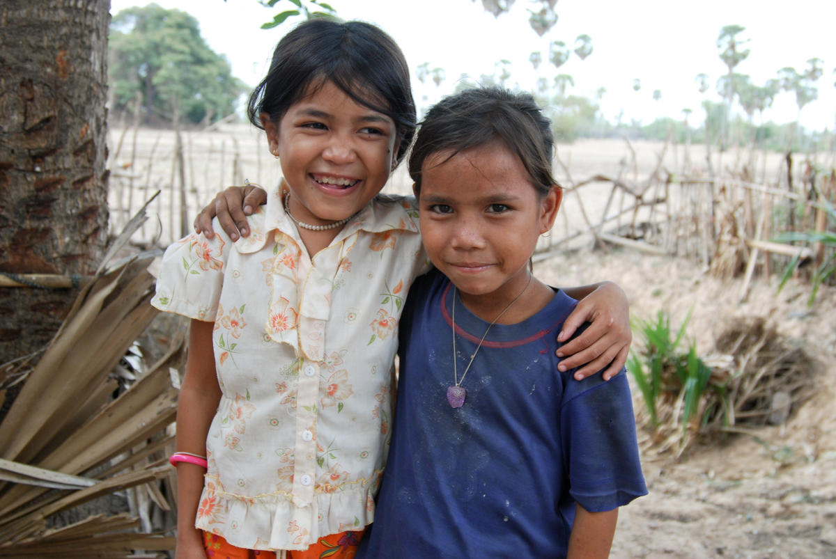 Two Khmer children stand together with their arms around each others shoulders