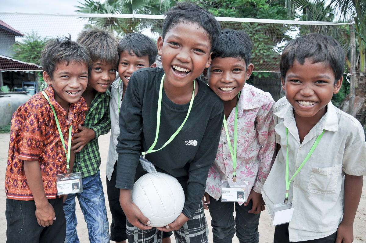 Group of three Khmer boys all smiling and laughing on outdoor volleyball court, Cambodia.