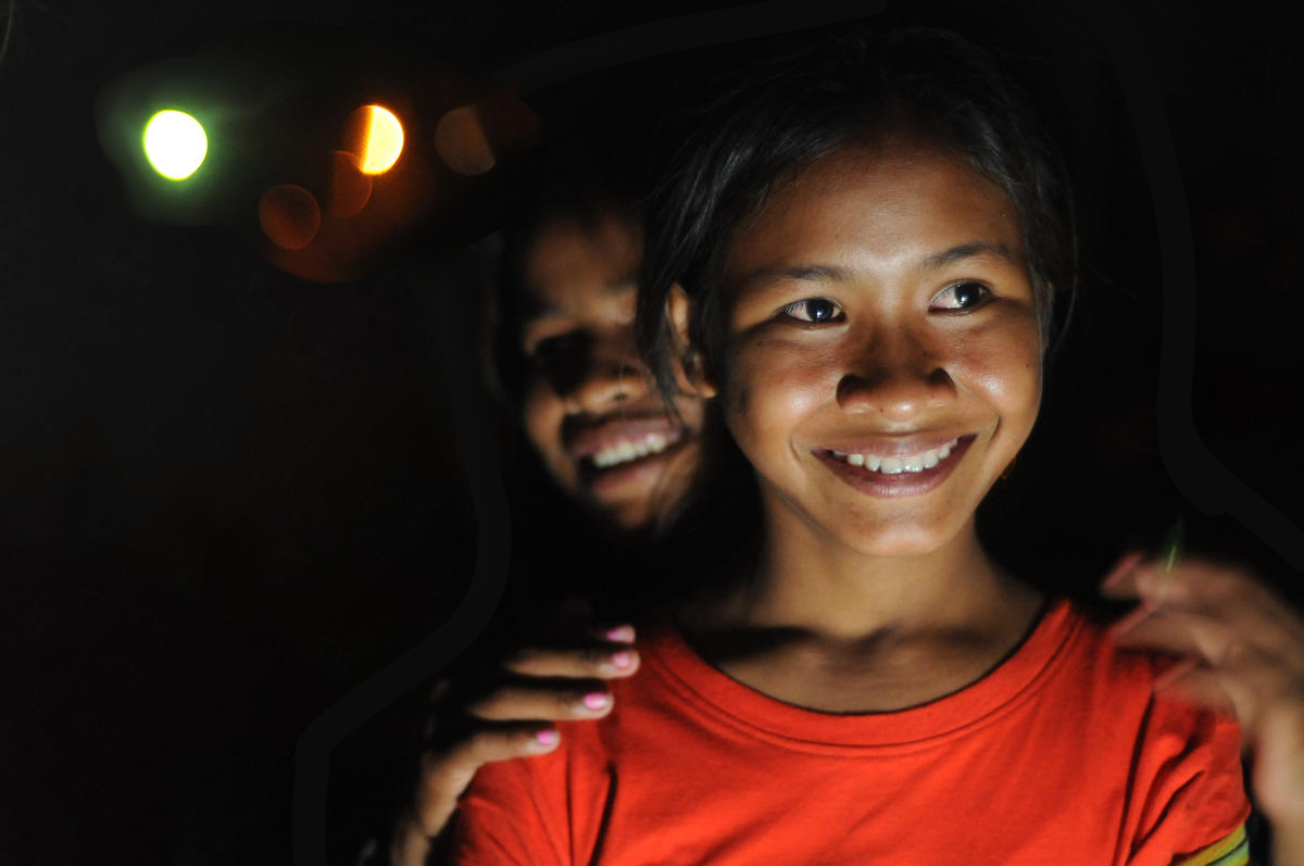 Two young Khmer women stand smiling, it is night time