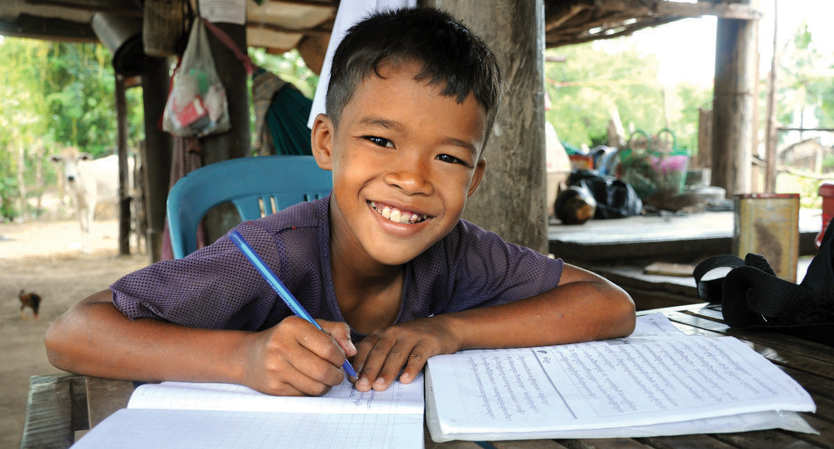 Khmer boy smiles at the camera with pen in hand, writing in his school books, Cambodia.