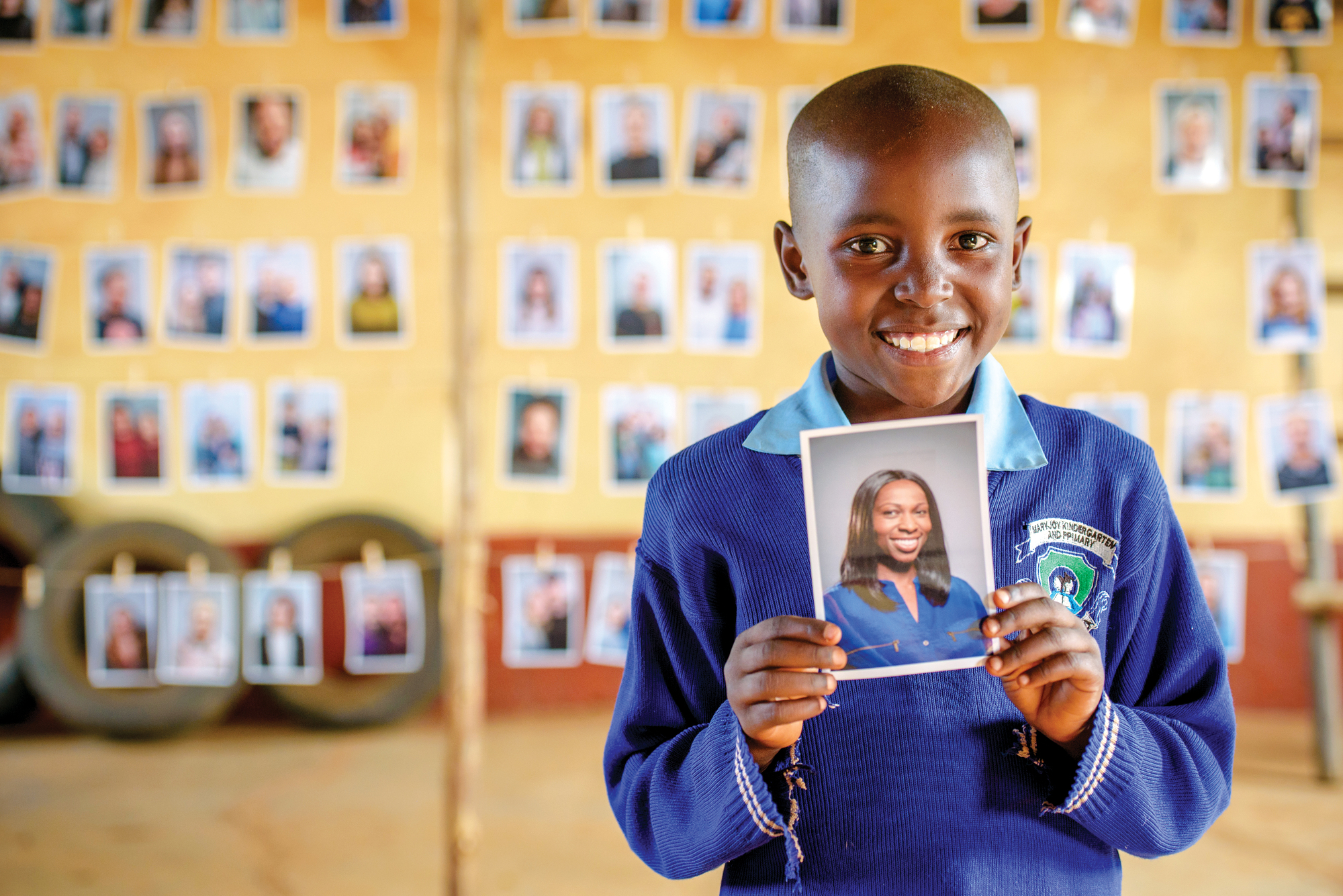 Nine-year-old Mary holds a picture of her sponsor that she chose.