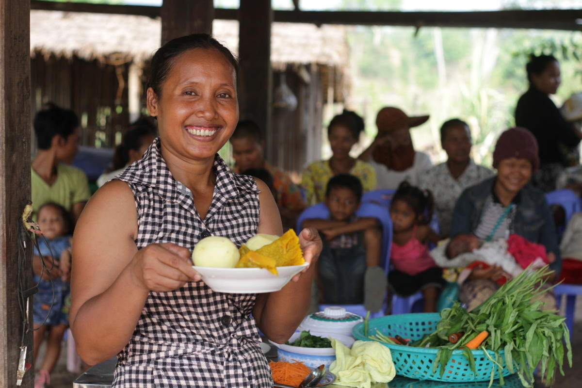 Khmer woman hold bowl of cut vegetables ready to do nutritious food cooking demonstration, Cambodia