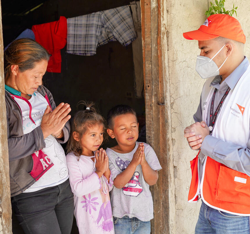 World Vision Staff pray with family in Honduras