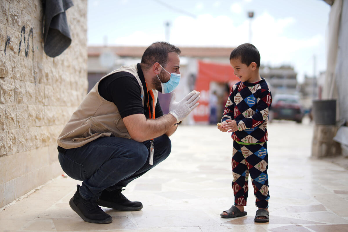 World Vision staff member speaks with young boy