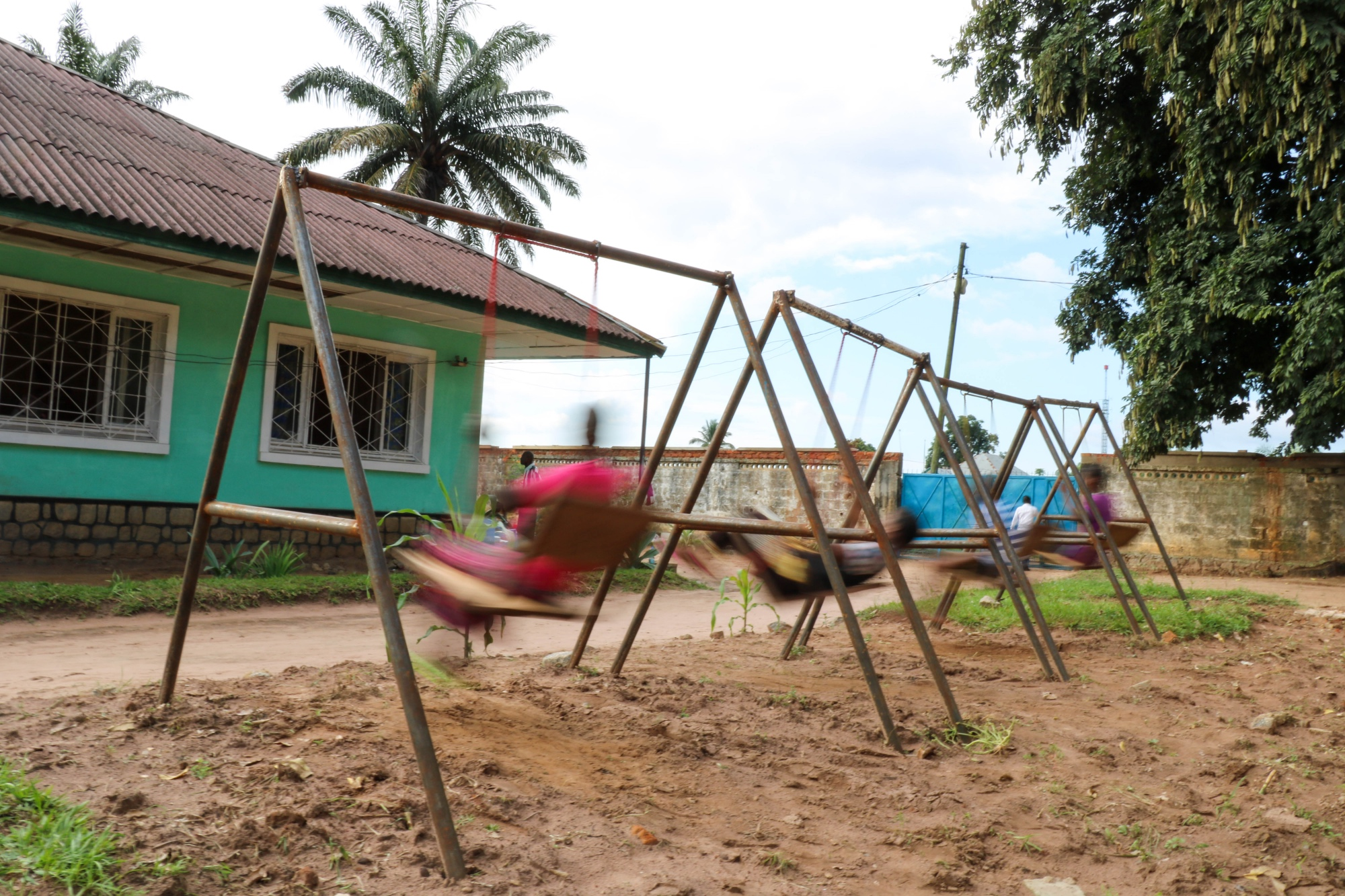 Four former militia members play on the swings at a centre for demobilised children in Kasai Central.  Forcibly recruited or eager militia member, physical or psychological injuries, all four of them are laughing and playing together.
