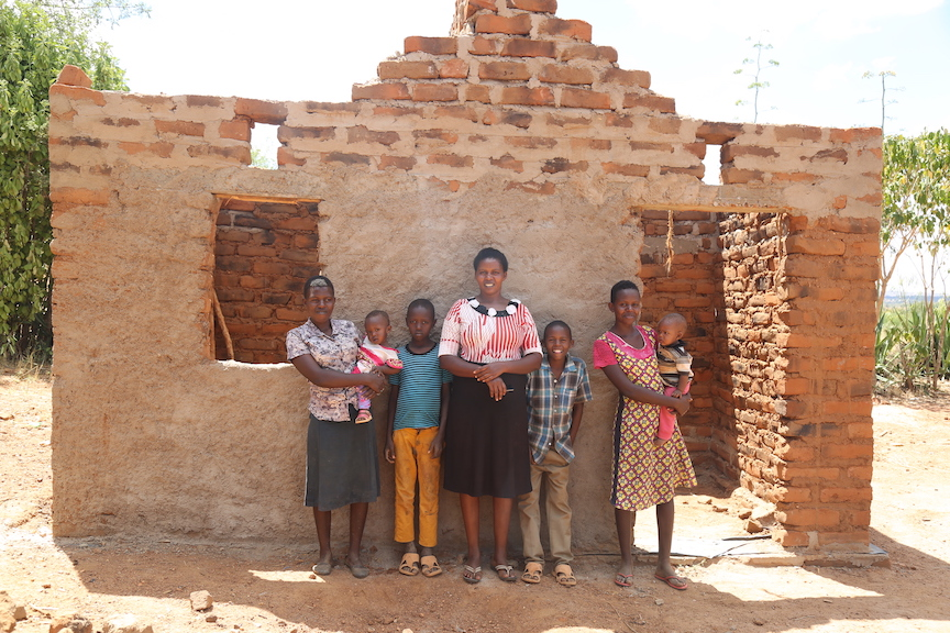 Janeffar and her family outside the new house that is being constructed using bricks