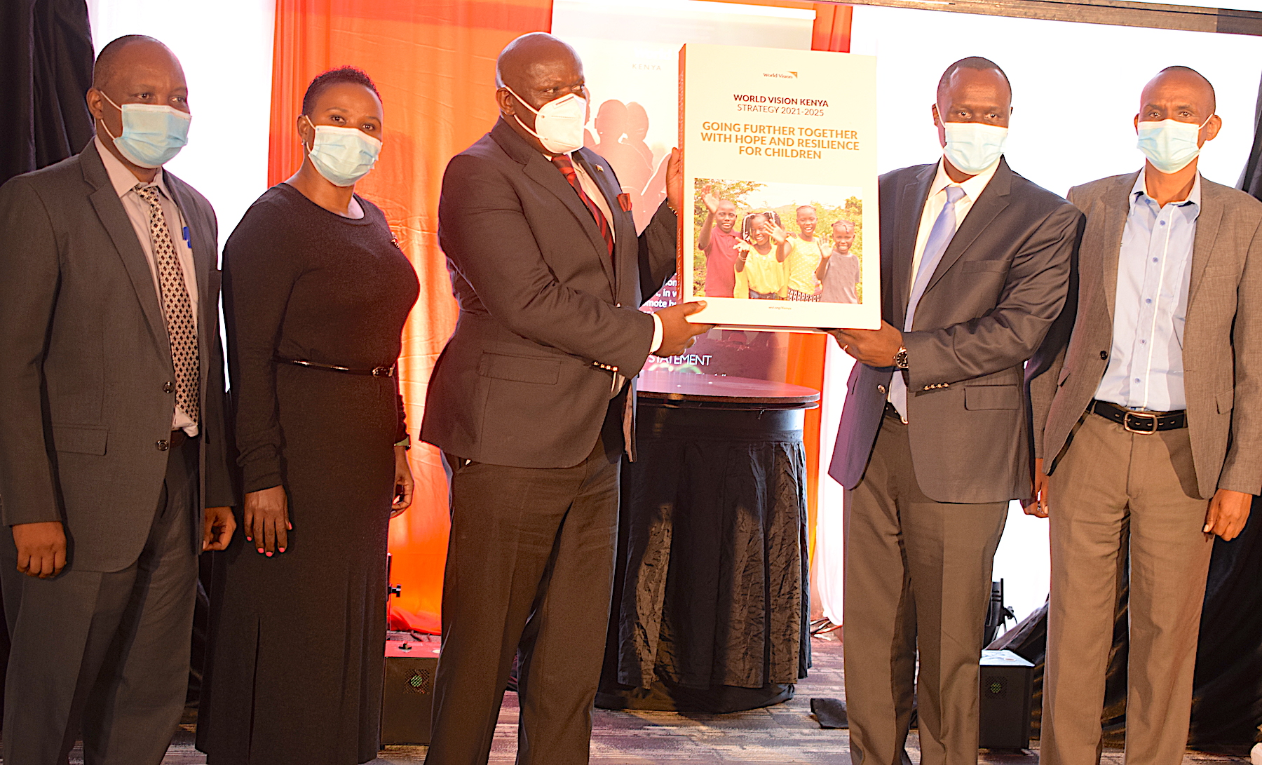 Left to right: Eric Wafukho (Chief Administrative Secretary for National Treasury & Planning for the government of Kenya) and Paul Lilan (World Vision Kenya Board Chair) hold the new five-year strategy (2021-2025) book for World Vision Kenya during the launch ceremony. ©World Vision Photo/Kenya.