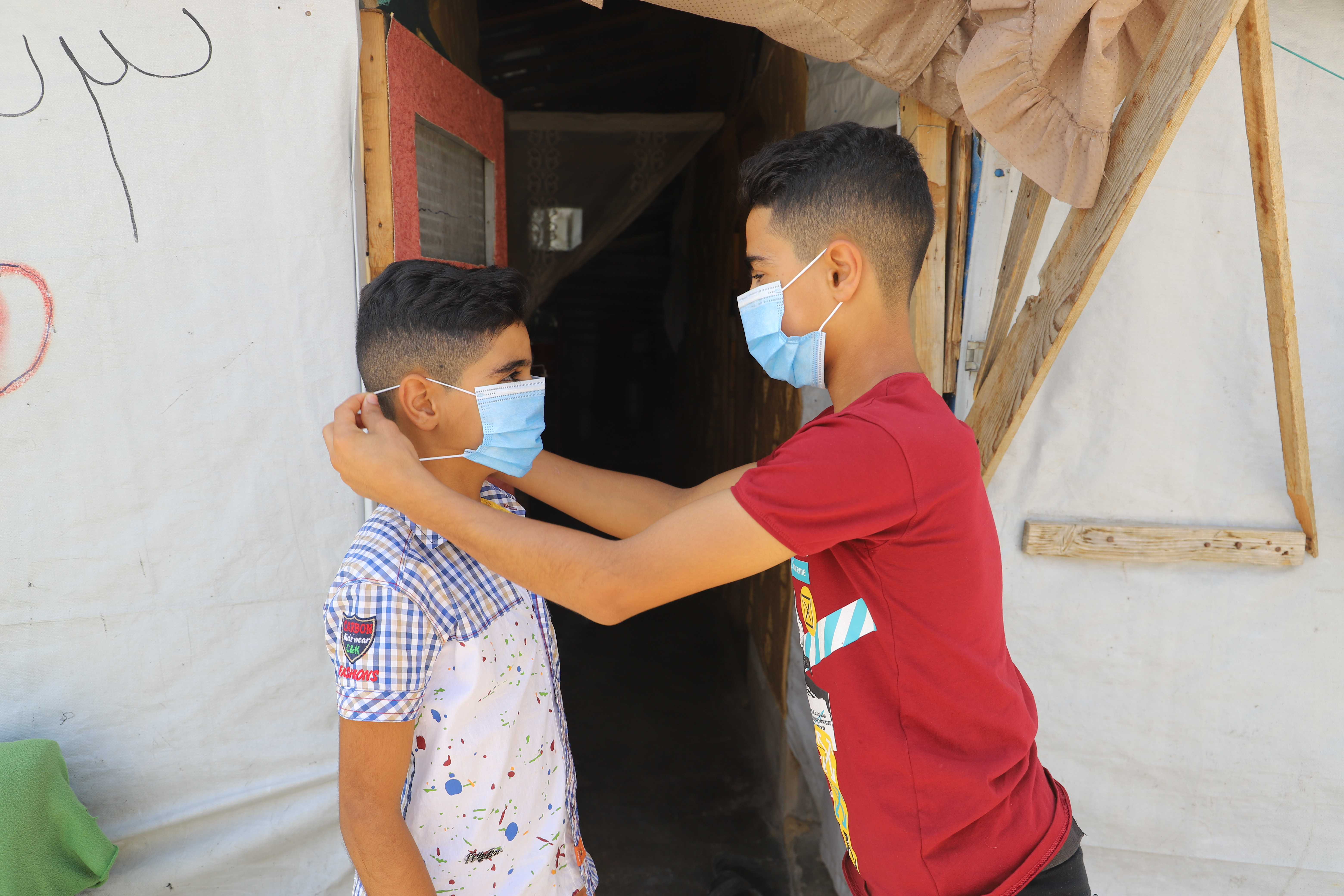 Ahmad putting a mask on his brother's face to keep him safe