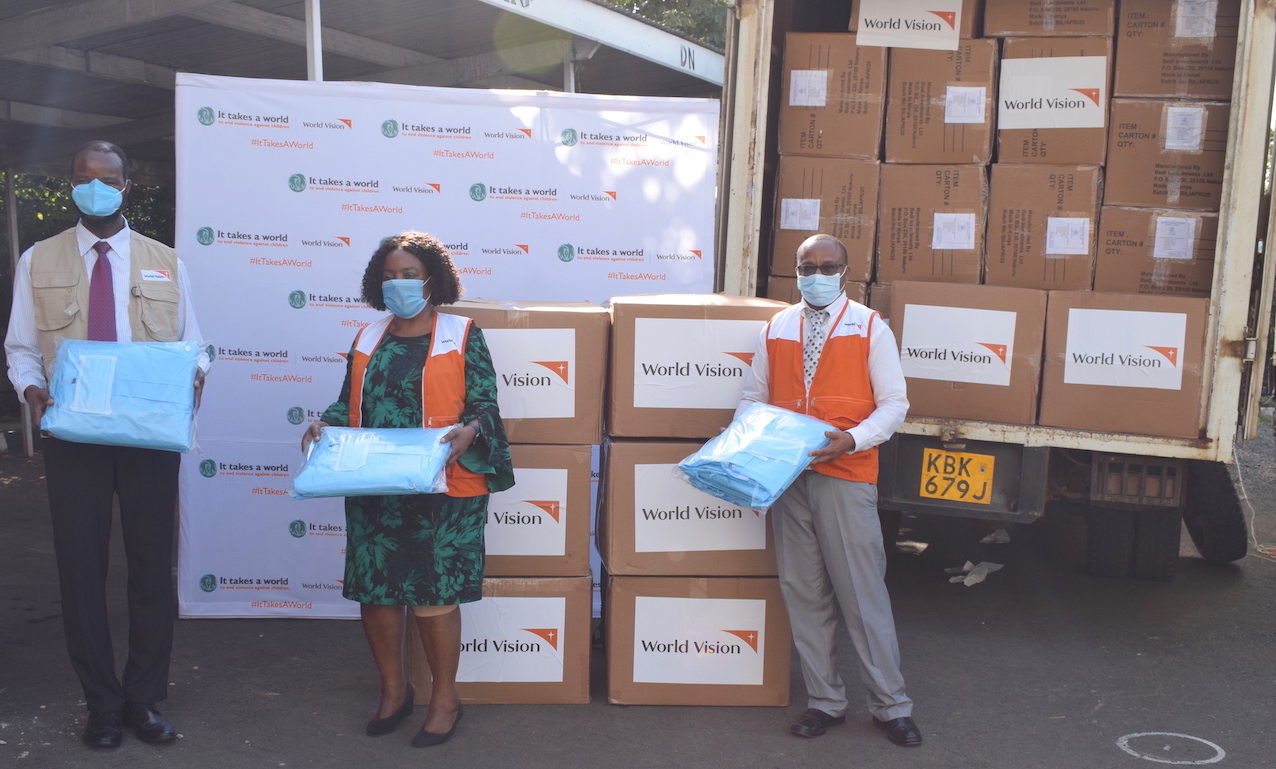 Dr. Stephen Omollo (Vice President for World Vision in East Africa), Lilian Dodzo (National Director for World Vision Kenya) & Gershon Mwakazi (COVID-19 Response Director for World Vision Kenya)holding some of the  Personal Protective Equipment kits donated to Ministry of Health. The kits contain surgical masks, shoe covers, scrub bottoms, aprons and coveralls.©World Vision Photo