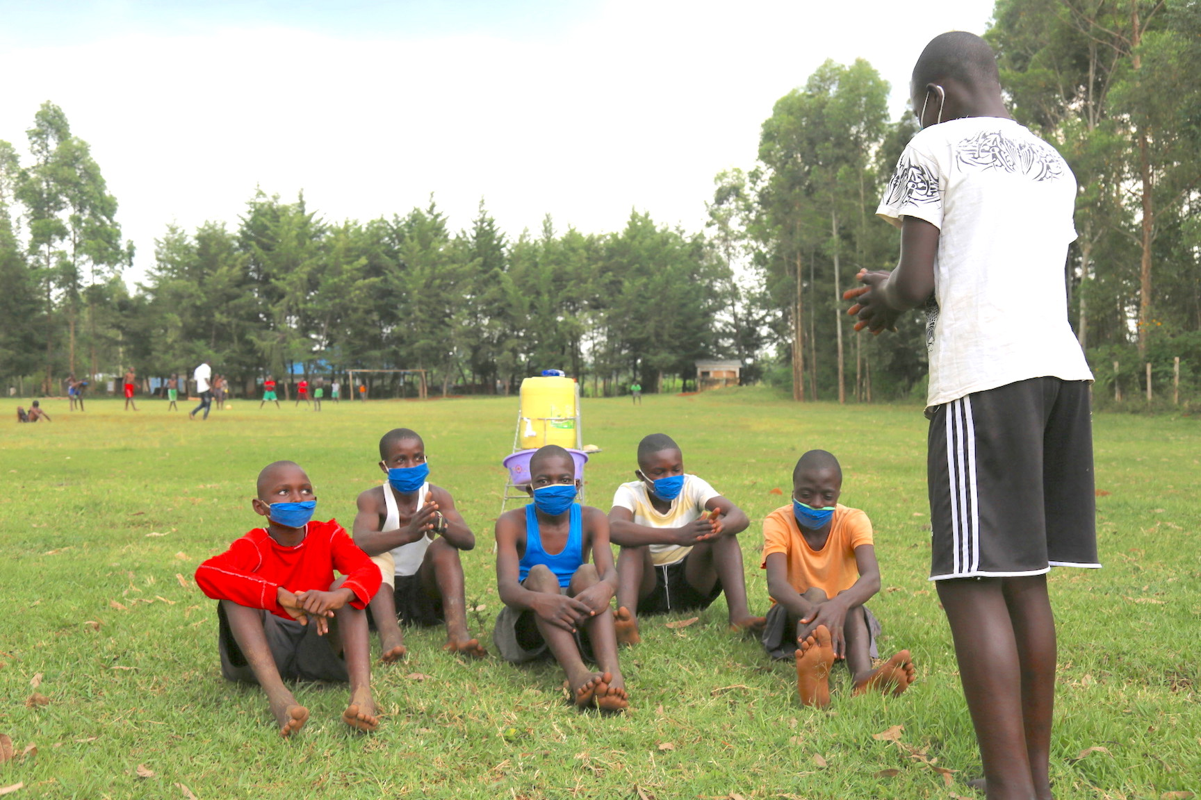 Raphael sensitises his friends on COVID-19 prevention strategies before they begin playing football.©World Vision Photo/Irene Sinoya.