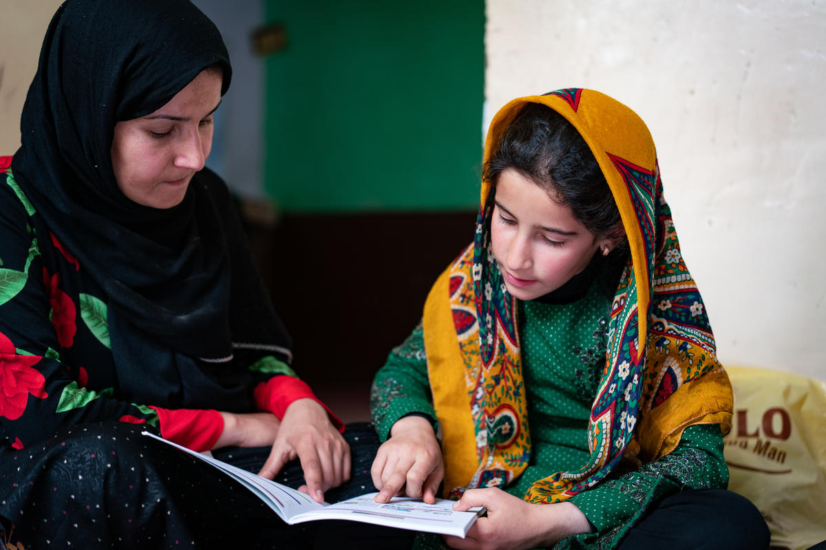 Rowaida helps her 11-year-old daughter Ilham read in Afghanistan, realising her dreams for a better future. Brett Tarver/World Vision