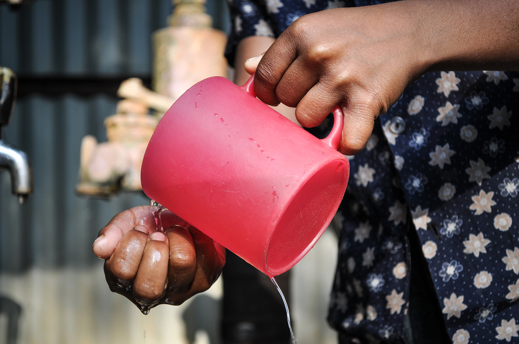 A woman pours water from a cup in Bangladesh