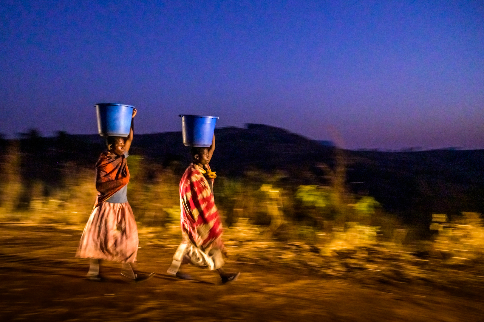 For Happiness (front) and her twin sister Gift, their first walk for water begins before dawn. Each day around the world, women and girls in developing countries walk an average of 6 kilometers for water that is often contaminated