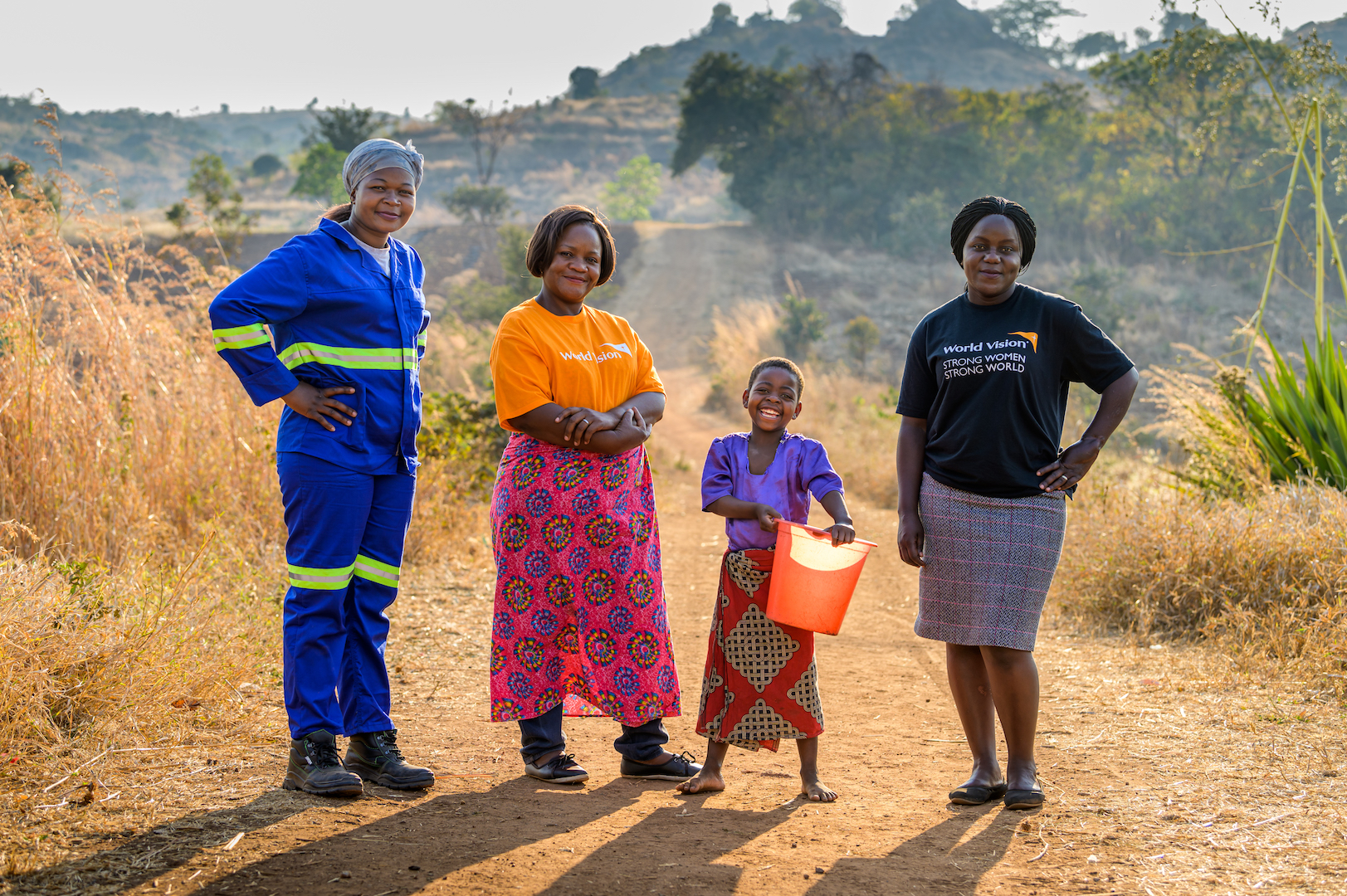 Strength also comes in the form of World Vision staff Liddah Manyozo, Mereena Mhone John, and Irene Chongwe (left to right with Ireen), who are coming alongside her family to promote change through clean water and sponsorship.