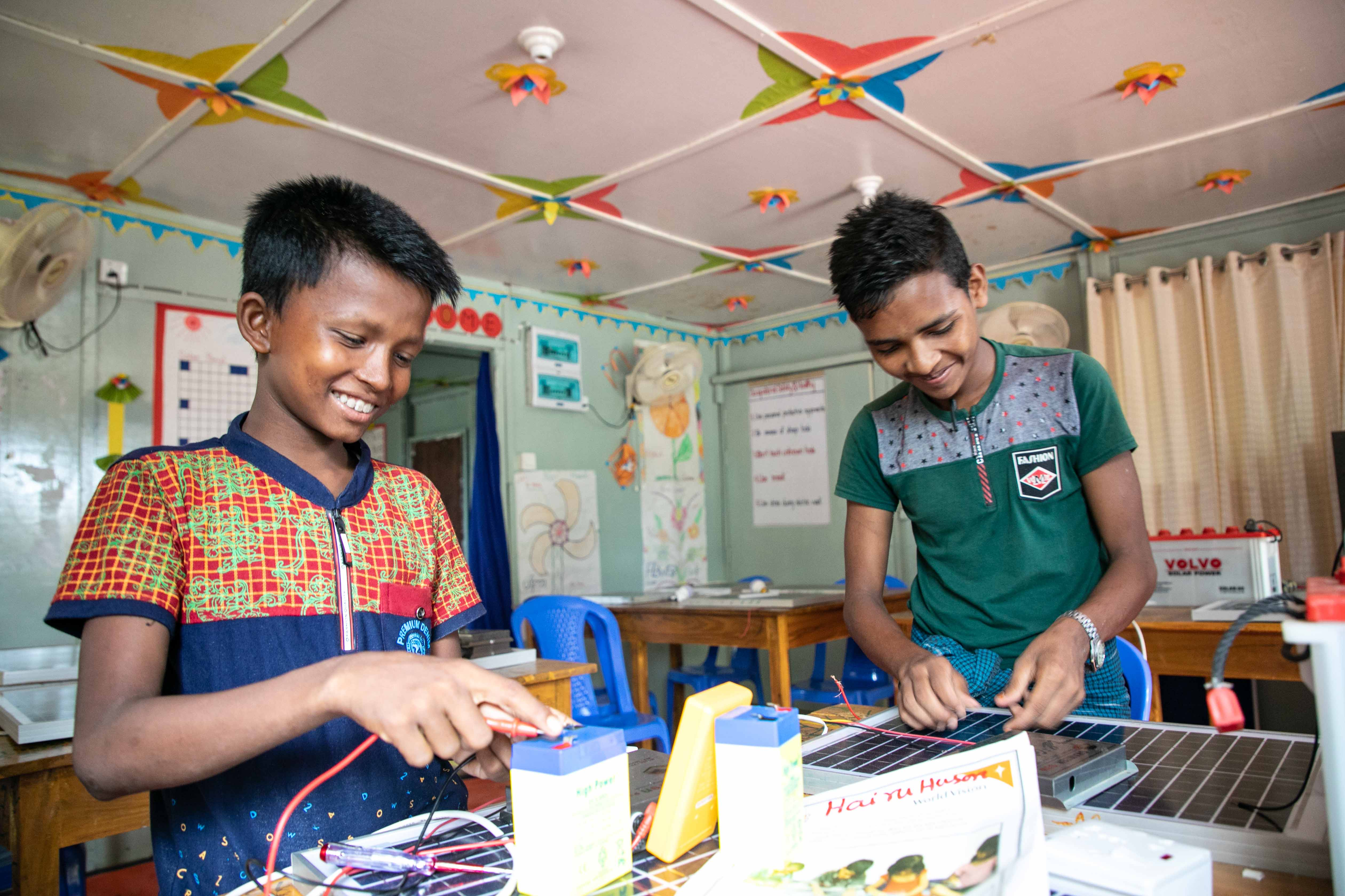 EDUCATION:  Adolescent boys enjoy learning solar panel and light repair at World Vision's multi-purpose centre.