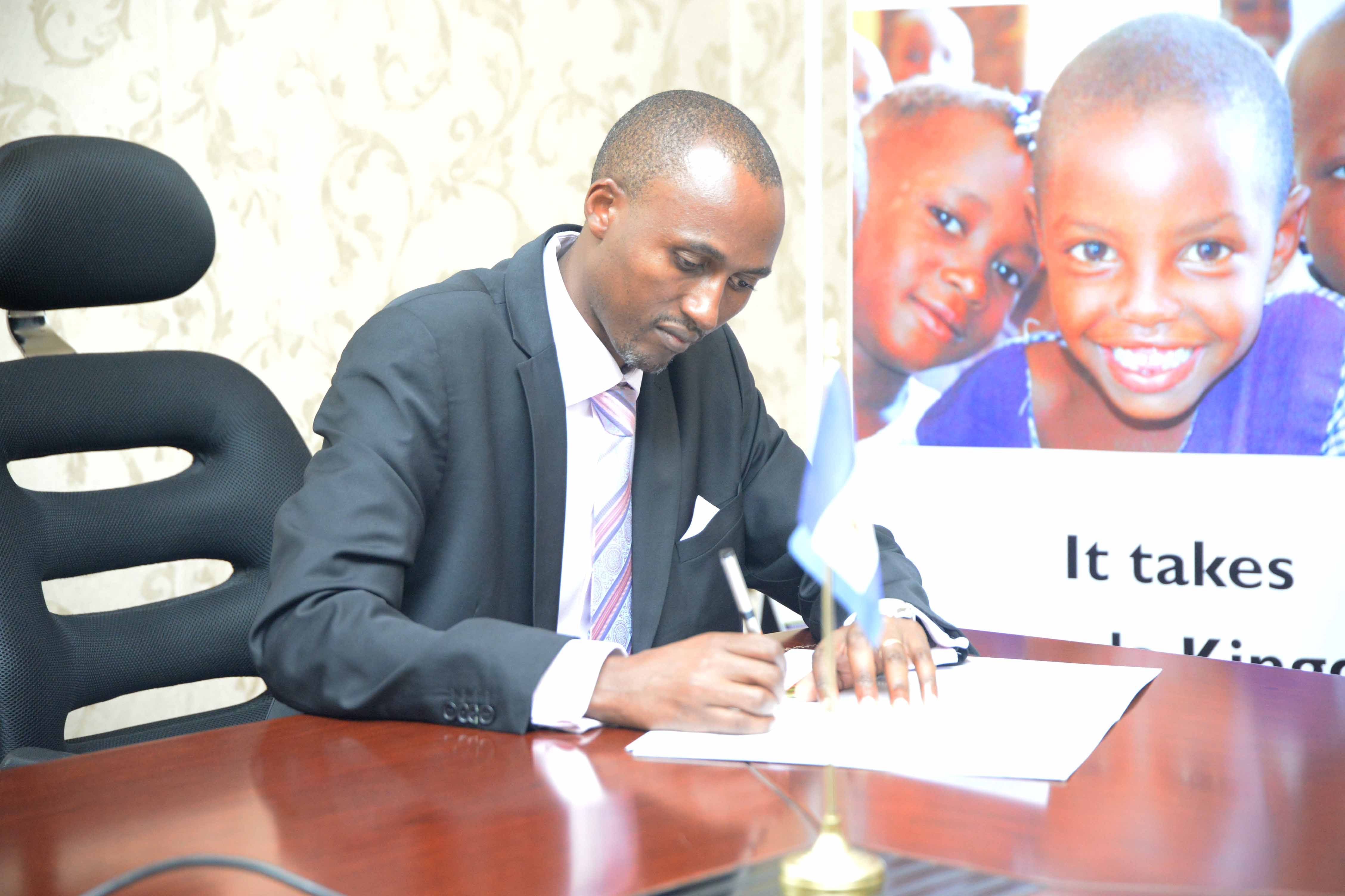 Jeremiah Nyagah, operations director for World Vision in Uganda signs the MOU between World Vision and the Buganda kingdom