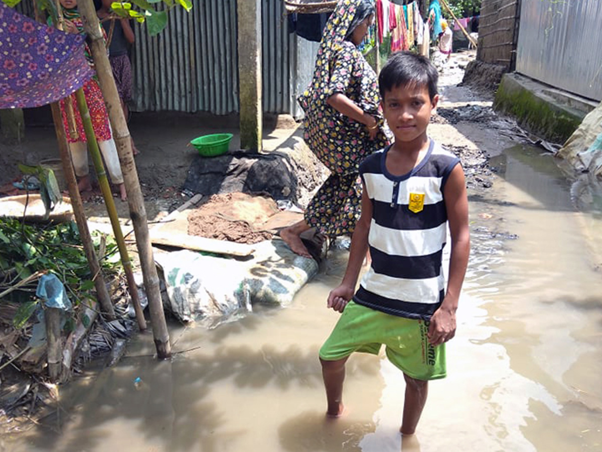 Kibria (10), sponsored child of World Vision Bangladesh standing on the water in their yard