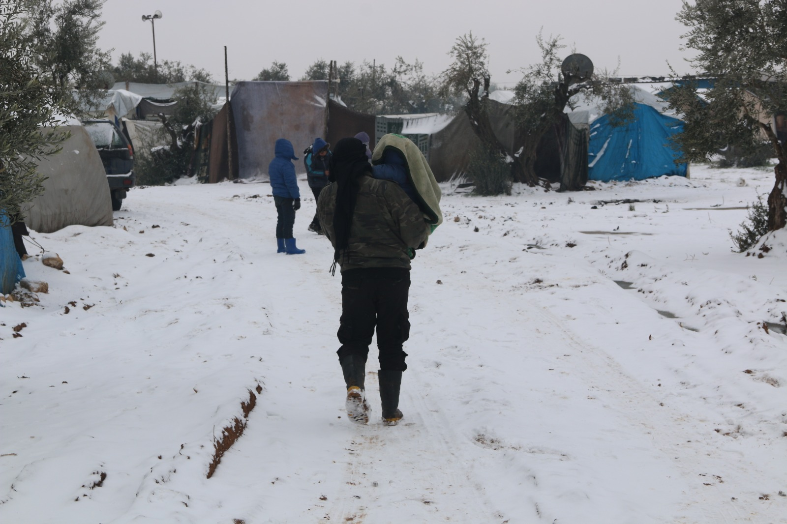 Displaced Syrian families in an informal displacement camp covered in snow.