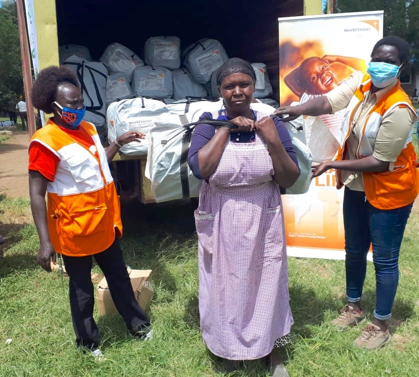 Ngendo receives Non Food Items (NFI) kits from World Vision staff at a camp for people affected by floods at Ndabibi in Nakuru County, Kenya. ©World Vision Photo.