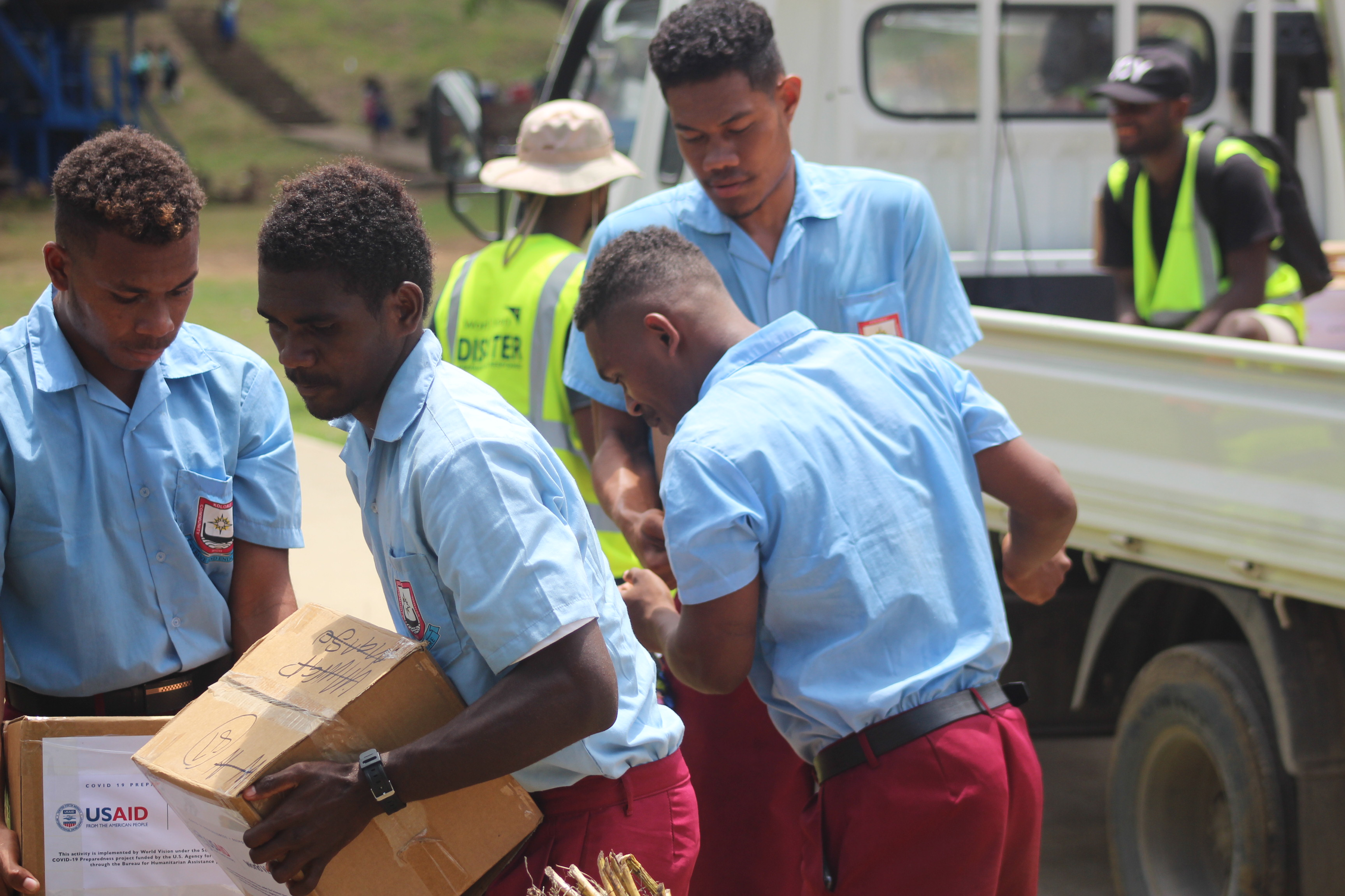 Koloale Community High School Students help to unload cartons of soaps from truck.