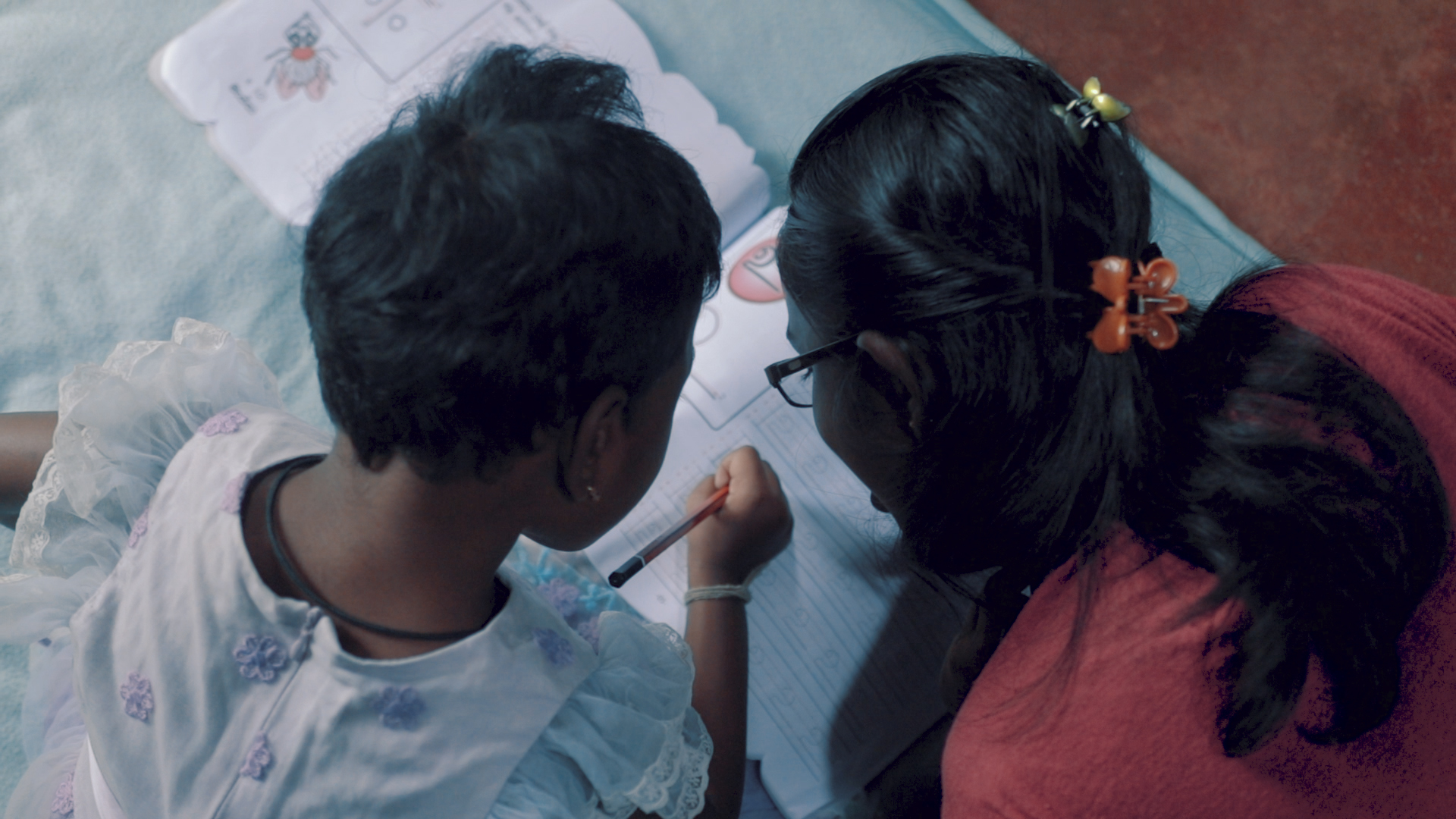 Maduwarshini learning to scribble with her sister