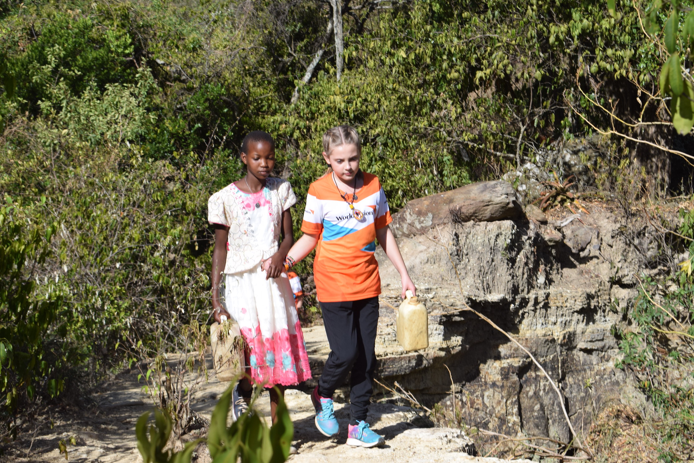 Maurine (left) shows Addyson the path she used to follow to fetch contaminated water.©World Vision/Photo by Sarah Ooko