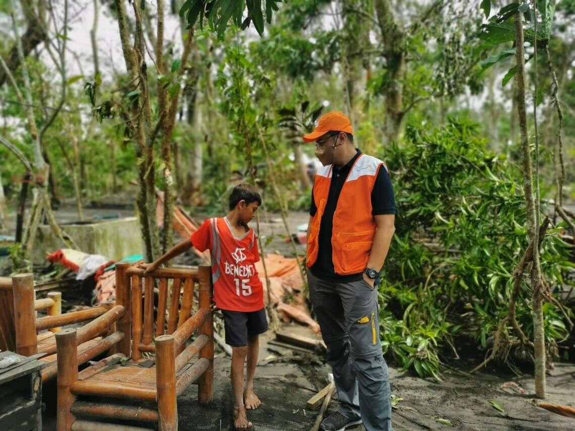 Mico speaks to a member of World Vision Philippines' disaster response team.