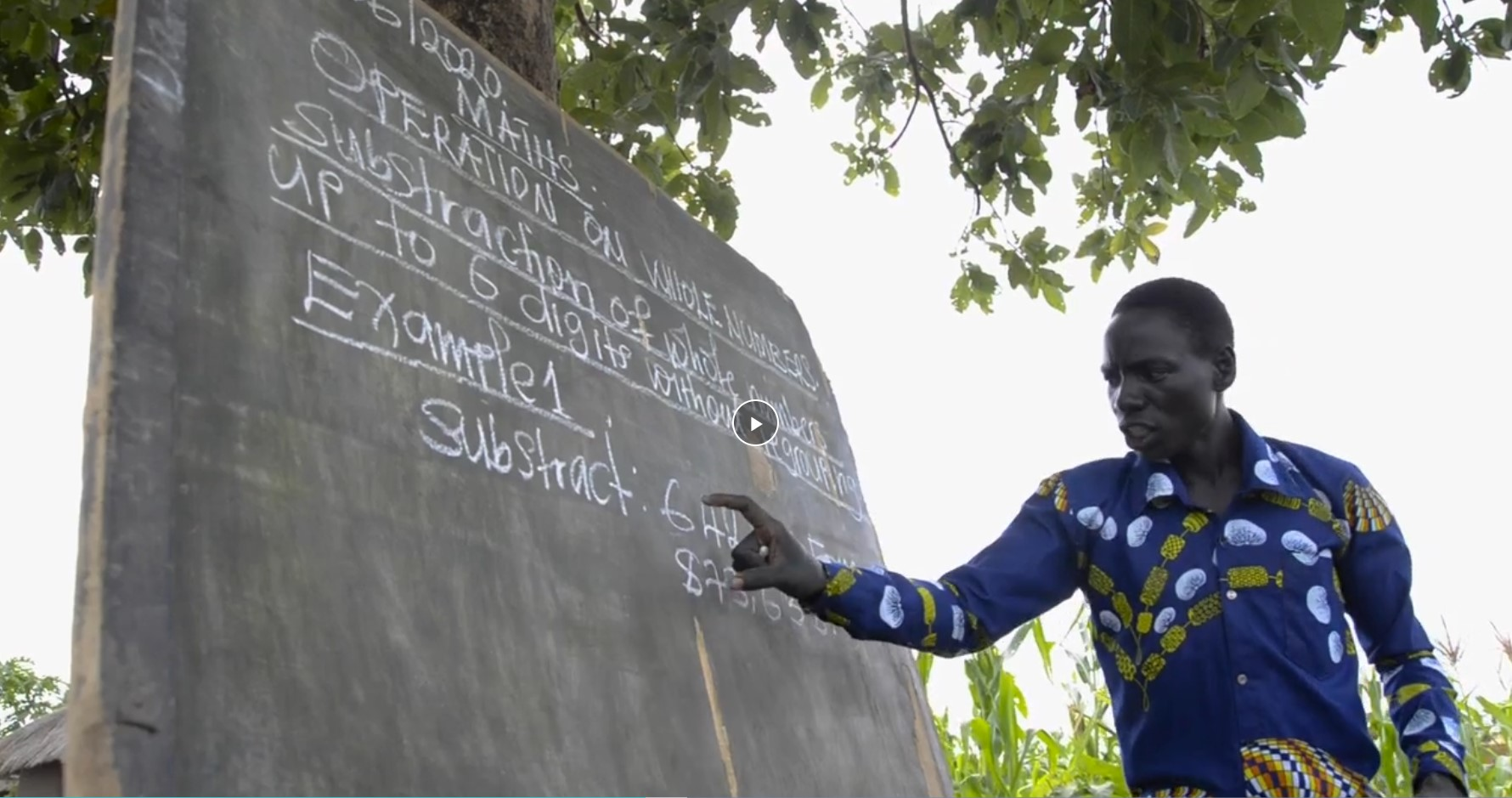 Santos teaches math to students in the open in Uganda