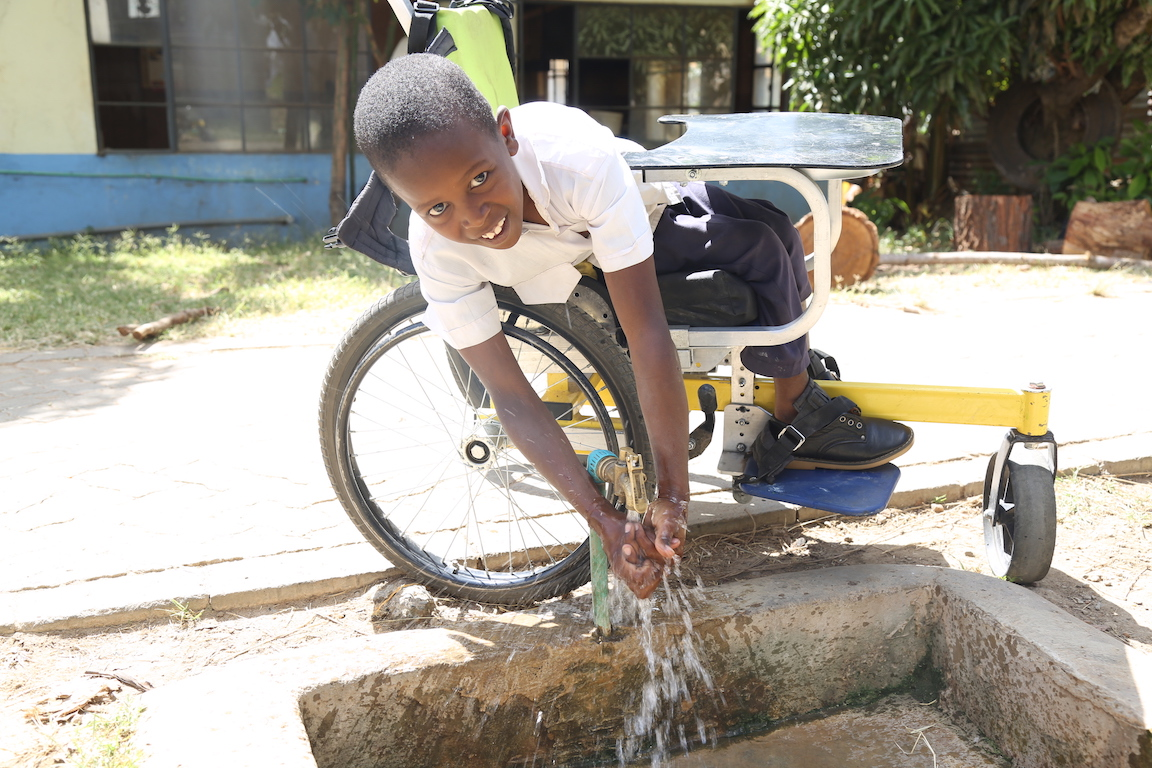 The wheelchair allows Gift to perform tasks such as washing hands independently. ©World Vision Photo/By Hellen Owuor.