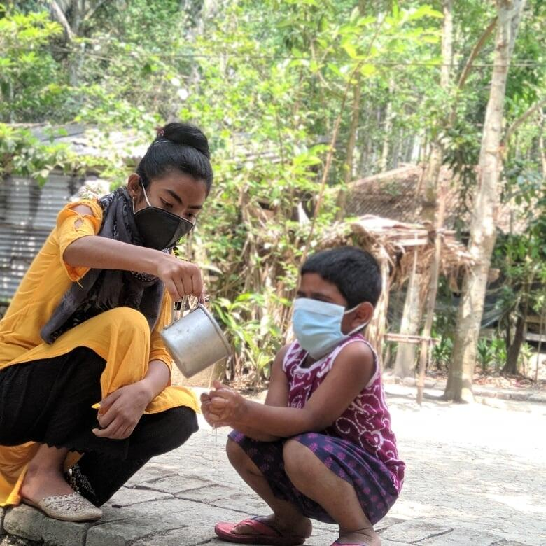 Young girl in Bangladesh helps a young boy properly wash his hands to protect himself from COVID-19