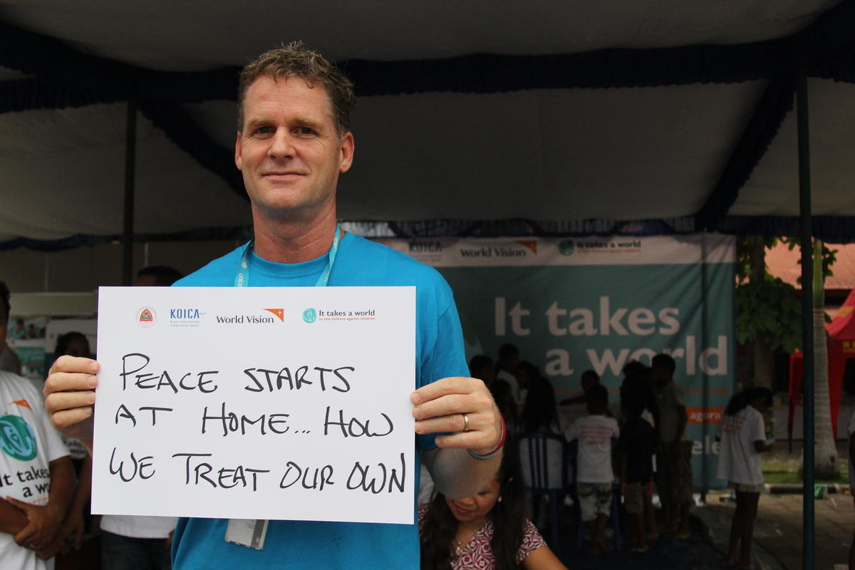 UNICEF Deputy Director holds a sign saying peace starts at home how we treat our own