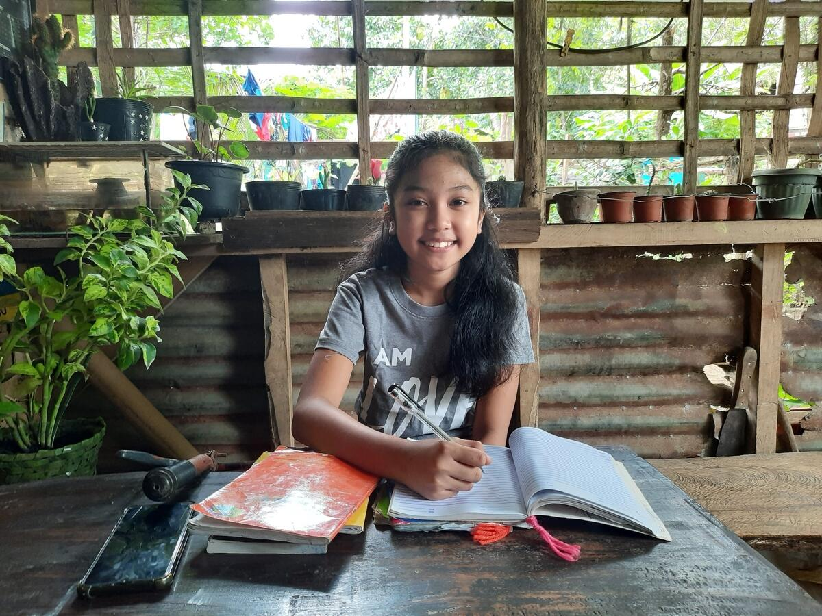 Nexi sits with her books on her desk to learn in the Philippines